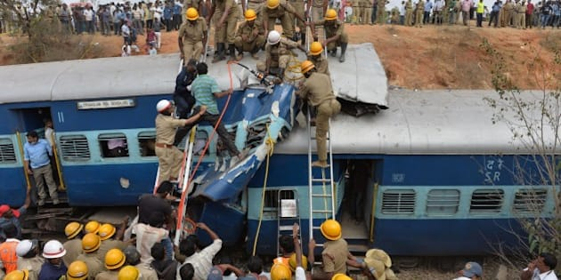 Crowds watch as Indian fire force personnel attempt to retrieve the bodies of victims from the Bangalore-Ernakulam train which derailed after a boulder fell on the track in Bidaragere, about 50 kms from Bangalore on February 13, 201.  At least five passengers were killed and more than 60 injured, according to local Press Trust of India (PTI) when the Bangalore-Ernakulam Inter City Express derailed.   AFP PHOTO / Manjunath KIRAN        (Photo credit should read Manjunath Kiran/AFP/Getty Images)