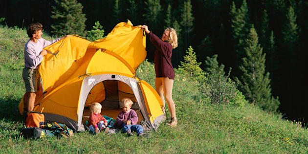 Mother and father pitching tent on mountain