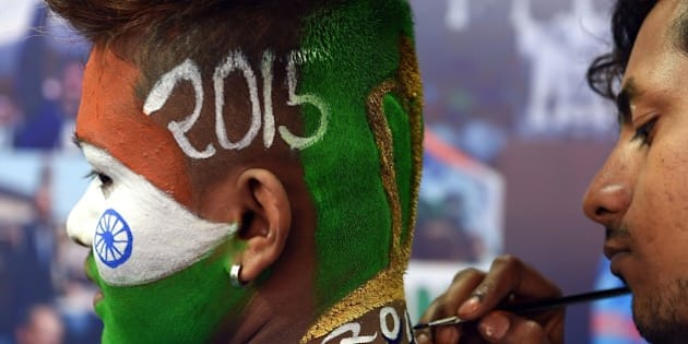 An Indian cricket enthusiast gets his face painted in the colours of his national flag at a salon offering special Cricket World Cup-themed hair styling in Mumbai on February 12, 2015. India, the defending champions, will meet arch-rivals Pakistan on February 15. Australia and New Zealand are due to co-host the forthcoming Cricket World Cup event in which 49 matches will be played across 14 venues between February 14-March 29. AFP PHOTO / INDRANIL MUKHERJEE        (Photo credit should read INDRANIL MUKHERJEE/AFP/Getty Images)