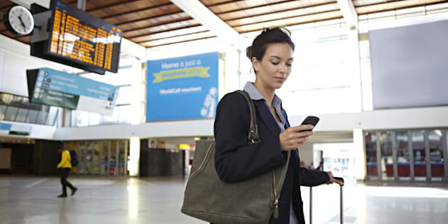 Businesswoman looking at smart phone in train station foyer