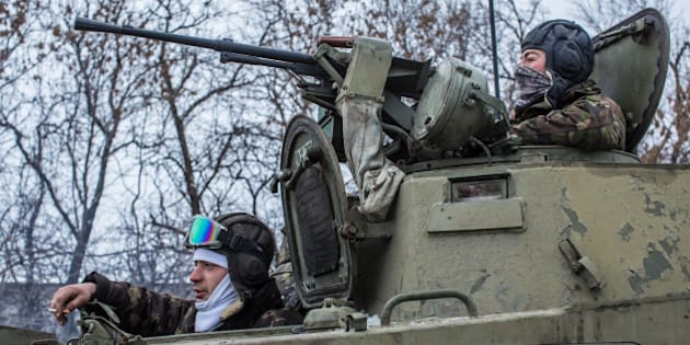 ARTEMIVSK, UKRAINE - FEBRUARY 16: Ukrainian soldiers prepare to drive in the direction of the embattled town of Debaltseve on February 16, 2015 in Artemivsk, Ukraine. A ceasefire that went into effect two days ago has been generally respected aside from Debaltseve, where pro-Russian rebels claim to have surrounded thousands of Ukrainian fighters and the battle continues. (Photo by Brendan Hoffman/Getty Images)
