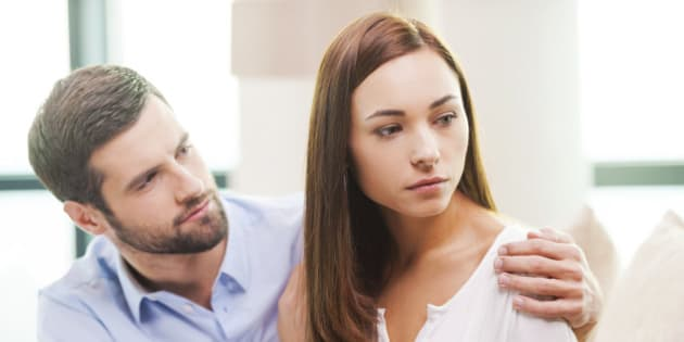 Depressed young woman looking away while man sitting behind her on the couch and consoling her
