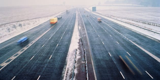 Motorway in winter, clear lanes surrounded by snow, elevated view