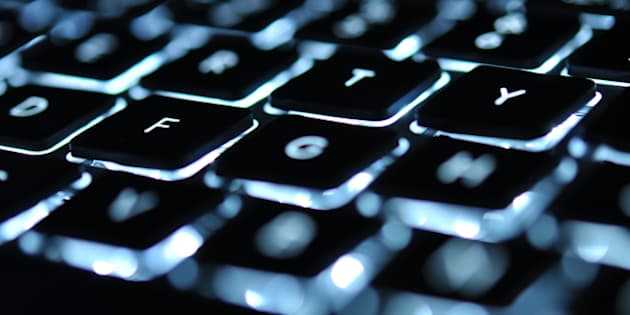 Backlit keyboard of laptop with letter F in focus.