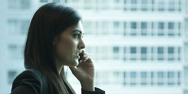 Indian businesswoman talking on cell phone in office