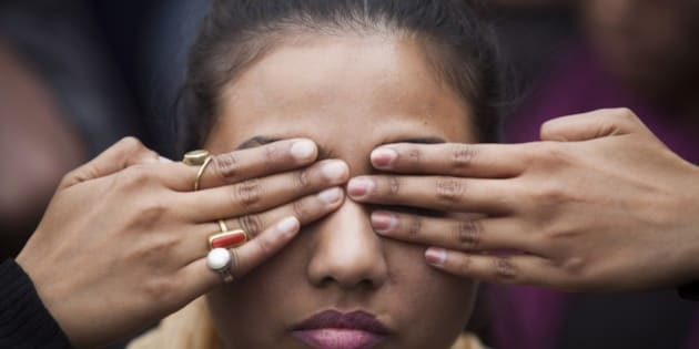 In this Dec. 15, 2014 photo, an Indian girl participates in a street play to create awareness on violence against women during a protest ahead of the second anniversary of the deadly gang rape of a 23-year-old physiotherapy student on a bus, in New Delhi, India. The case sparked public outrage and helped make women's safety a common topic of conversation in a country where rape is often viewed as a woman's personal shame to bear. (AP Photo/Tsering Topgyal)