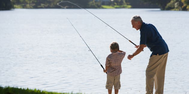 Man and young boy outdoors at park fishing in a lake