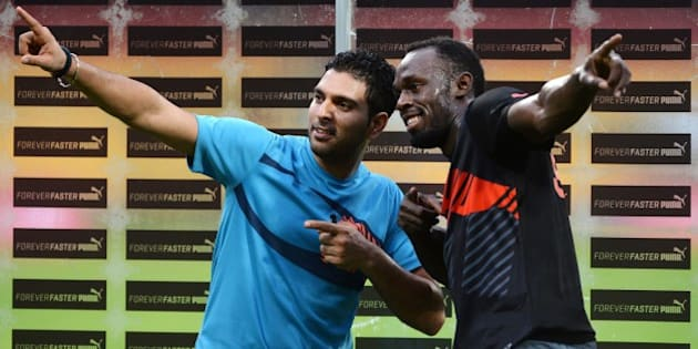 Jamaican Olympic Champion sprinter Usain Bolt (R) and Indian cricketer Yuvraj Singh pose for a photograph after a four-over exhibition match led by the sport stars at Chinnaswamy Stadium in Bangalore on September 2, 2014. Bolt, on his first-ever visit to India, took part in an exhibition cricket match with some of India's top players.  AFP PHOTO/Manjunath KIRAN        (Photo credit should read Manjunath Kiran/AFP/Getty Images)
