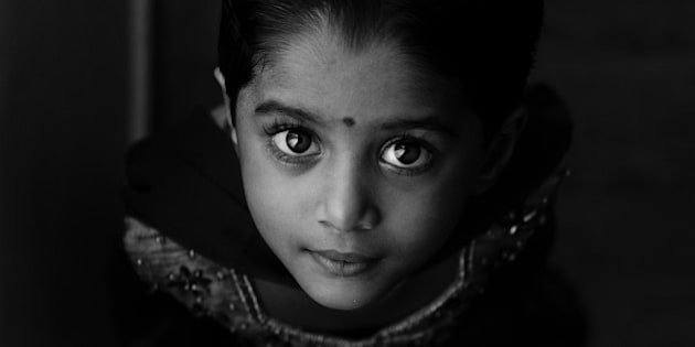 Indian girl Child in traditional dress looking up. Black and white shot. Window lit.
