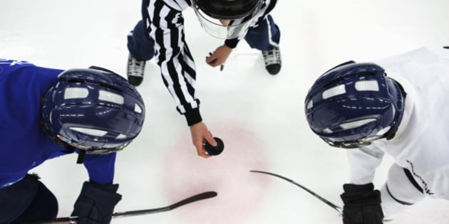Directly above shot of referee and two ice hockey players in face-off