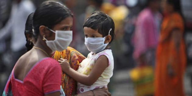 An Indian woman and a child cover themselves with protective masks after the news of the outbreak of swine flu virus as they walk inside the premises of Gandhi Hospital in Hyderabad, India, Wednesday, Jan. 21, 2015. According to local reports, nine people died at the state-run hospital. (AP Photo/Mahesh Kumar A.)