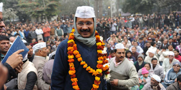 India's Aam Aadmi Party (Common Man's Party) leader Arvind Kejriwal (C) is greeted by supporters as he arrives at a public meeting in New Delhi on December 22, 2013.   India's anti-graft crusader Arvind Kejriwal has vowed to punish corrupt ministers and clean up 'dirty politics' in a fiery speech that hinted at a decision to form government in Delhi. Kejriwal, a former civil servant turned politician, has been under mounting pressure to form a coalition government in Delhi since his party's stunning showing at December 4 state elections.  AFP PHOTO/SAJJAD HUSSAIN        (Photo credit should read SAJJAD HUSSAIN/AFP/Getty Images)