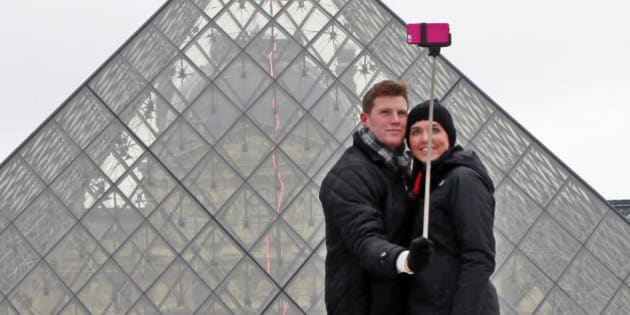 Chris Baker and Jennifer Hinson from Nashville, Tennessee, use a selfie stick in front of the Louvre Pyramide in Paris, Tuesday, Jan. 6, 2015. Selfie sticks have become enormously popular among tourists because you dont have to ask strangers to take your picture, and unlike hand-held selfies, you can capture a wider view without showing your arm. But some people find selfie sticks obnoxious, arguing that they detract from the travel experience. (AP Photo/Remy de la Mauviniere)