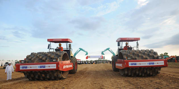 Heavy tractors drive at the ground-breaking ceremony during the Commencement Ceremony of Thilawa Special Economic Zone Project in Thilawa, on the outskirts of Yangon on November 30, 2013.  Thilawa SEZ (Special Economic Zone) will be built on 2400 hectares of land on the outskirts of Yangon. AFP PHOTO/ SOE THAN WIN        (Photo credit should read Soe Than WIN/AFP/Getty Images)