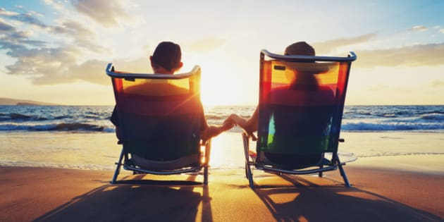 senior couple sitting on the beach watching sunset