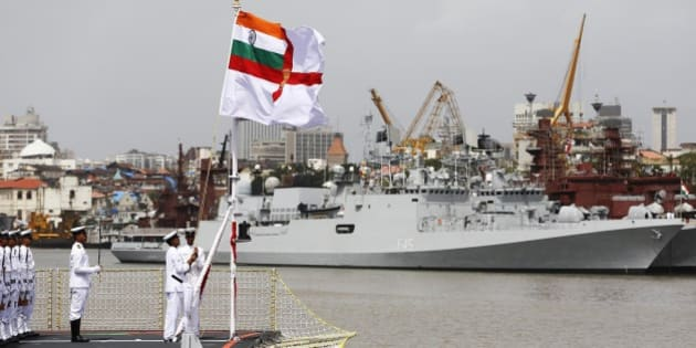Indian naval officers hoists the navy flag during a ceremony to induct the largest indigenously built warship INS Kolkata in Mumbai, India, Saturday, Aug. 16, 2014. (AP Photo/Rajanish Kakade)
