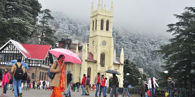 SHIMLA, INDIA - JANUARY 14: People walking at the ridge during snowfall in the backdrop of snow covered Jhaku hill on January 14, 2015 in Shimla, India. Shimla and its surrounding resorts of Kufri, Fagu and Narkanda had another spell of fresh snow while Dhauladhar ranges in Kangra, Churdhar ranges in Sirmaur, Rohtang Pass and higher hills in Chamba district experienced heavy snowfall, throwing normal life out of gear. (Photo by Santosh Rawat/Hindustan Times via Getty Images)