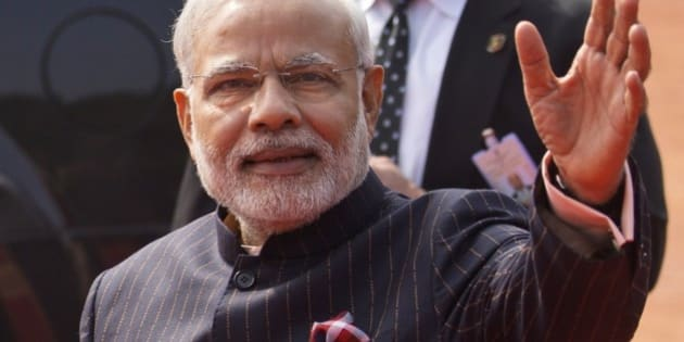 In this Jan.25, 2015 photo, Indian Prime Minister Narendra Modi wears a dark pinstriped suit with his name monogrammed in dull gold stripes during a reception to U.S. President Barack Obama in New Delhi, India. The suit which became controversial after its photographs went viral on social media was to be auctioned in his home state of Gujarat, over the next three days starting Wednesday, Feb.18, 2015 officials said. (AP Photo/Saurabh Das)
