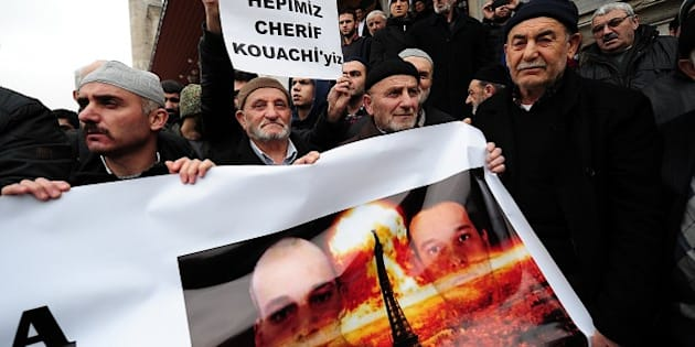 Turkish anti-Charlie Hebdo protesters hold a banner with pictures of Cherif and Said Kouachi (R), two Islamist gunmen who killed 12 people in an attack on Charlie Hebdo, during a demonstration against the depiction of the Prophet Mohammed by the French satirical weekly and mourning two Islamist gunmen who killed 12 people in an attack on Charlie Hebdo, in Istanbul on January 16, 2015. About 50 Turkish islamists gathered after friday prayer at Fatih Mosque to protest after the magazine published this week a 'survivors' issue featuring an image of the Prophet Mohammed weeping. AFP PHOTO/OZAN KOSE        (Photo credit should read OZAN KOSE/AFP/Getty Images)