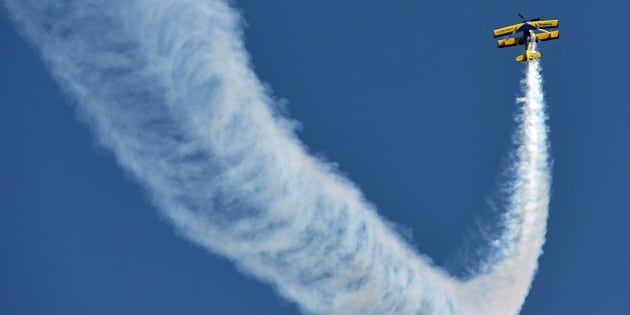 Britain's Breitling SkyWalkers Aerobatic Team members perform aerial stunts atop Boeing Stearman Biplane at Yelahanka Airforce Station in Bangalore on February 18, 2015, on the inaugural day of Aero India 2015. Prime Minister Narendra Modi has vowed to end India's status as the world's number one defence importer, saying he wanted 70 percent of hardware to be manufactured domestically by the turn of the decade. Speaking at the start of a major aviation industry conference, Modi told hundreds of foreign and local businessmen that his government would favour domestic firms when awarding defence contracts as part of a larger push to boost India's manufacturing sector.  AFP PHOTO/Manjunath KIRAN        (Photo credit should read MANJUNATH KIRAN/AFP/Getty Images)