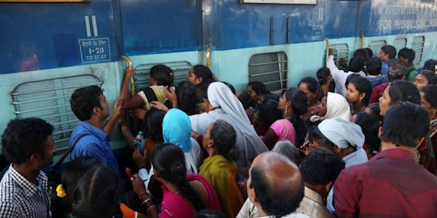 Indian women stand in front of a train door that was closed by a security officer asking them to first form a queue to enter, as people crowd a railway platform in Hyderabad, India, Saturday, Jan. 10, 2015. Railway platforms and trains were overcrowded Saturday as most people travelled to their hometowns to celebrate the Hindu festival of Makar Sankranti that falls on Jan. 14. (AP Photo/Mahesh Kumar A.)