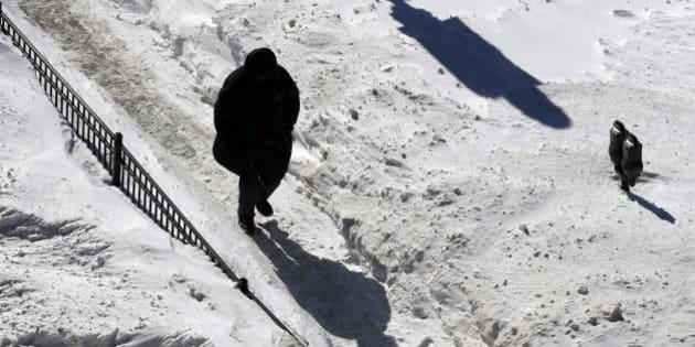 A man walks on a snow-covered sidewalk in Boston, Monday, Feb. 16, 2015. New England remained bitterly cold Monday after the region's fourth winter storm in a month blew through. (AP Photo/Michael Dwyer)