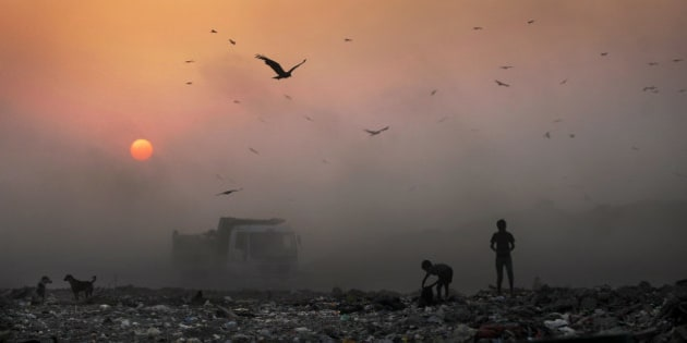 AP10ThingsToSee - A thick blanket of smoke is seen against the setting sun as young ragpickers search for reusable material at a garbage dump in New Delhi, India, Friday, Oct. 17, 2014. India launched the Air Quality Index Friday to measure air quality across the nation that is home to some of the most polluted cities in the world. (AP Photo/Altaf Qadri)
