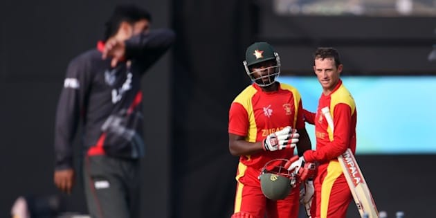 Zimbabwe batsmen Sean Williams (R) and Elton Chigumbura (2nd L) celebrate victory as United Arab Emirates (UAE) player Mohammad Naveed (L) reacts during their Pool B 2015 Cricket World Cup match in Nelson on February 19, 2015.    AFP PHOTO / William WEST        (Photo credit should read WILLIAM WEST/AFP/Getty Images)