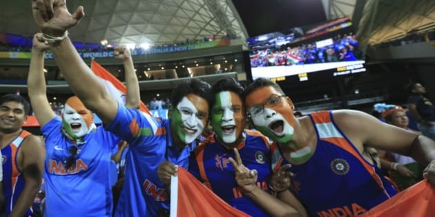 Indian cricket fans, face painted with colors of the Indian flag react to the camera after India won the World Cup Pool B match against Pakistan in Adelaide, Australia, Sunday, Feb. 15, 2015. (AP Photo/James Elsby)