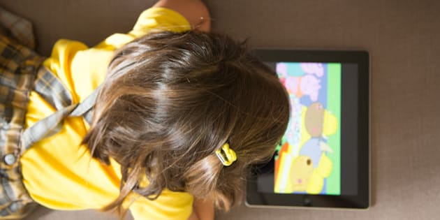 Girl watching cartoons online with the iPad tablet laying in the sofa at home with view from above.