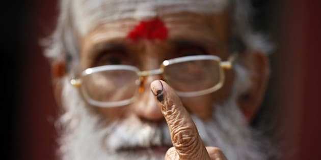 NEW DELHI, INDIA - FEBRUARY 7: A saint showing his inked finger after casting his vote during the Delhi Assembly Elections 2015, on February 7, 2015 in New Delhi, India. Delhi is headed for a record turnout on Saturday as more than 69.5% of the city's 1.33 crore voters cast their ballot till 5pm. After a slow start in the morning, polling picked up around noon, with scores of people queuing up at booths to exercise their franchise in an electrifying electoral battle that the national capital has never witnessed before. 69.5 per cent of 1.3 voters had been inked by 5 pm on Saturday, as Delhi looked set for a record turnout after a slow morning. There are 673 candidates in the fray now. Voting is taking place in 11,763 centers, located in schools. Many initial voters in middle class and posh areas were early morning walkers. (Photo by Raj K Raj/Hindustan Times via Getty Images)
