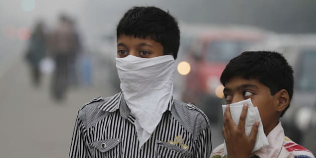 NEW DELHI, INDIA - NOVEMBER 7: Children cover their face to take precaution from the air pollution by a mixture of pollution and fog at NCR region on November 7, 2012 in New Delhi, India. (Photo by Sanjeev Verma/Hindustan Times via Getty Images)