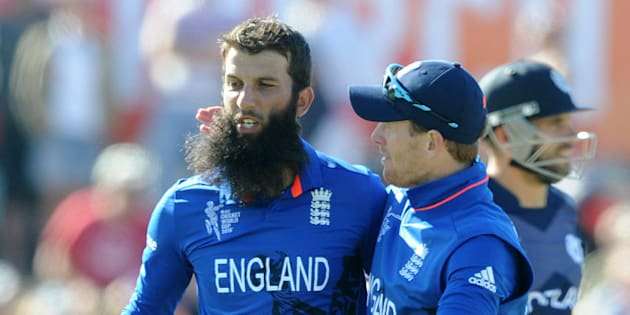 England's Moeen Ali left, is congratulated by his captain Eoin Morgan after taking the wicket of Scotland's Richie Berrington, right,  during their Cricket World Cup match in Christchurch, New Zealand, Monday, Feb. 23, 2015. (AP Photo Ross Setford)
