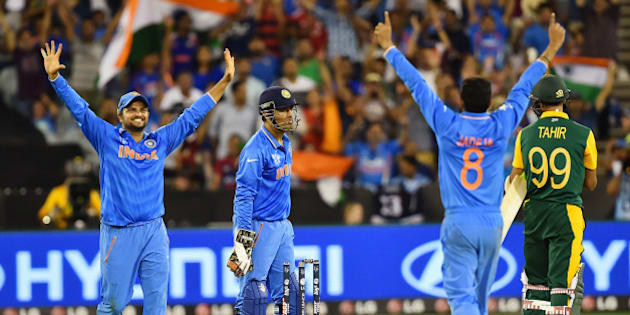 Indian player's  Suresh Raina,left, M S Dhoni and Ravindra Jadeja, second right, celebrate as South Africa's Muhammad Imran Tahir, right, stands on the pitch following their 130 run loss to India in their Cricket World Cup pool B match in Melbourne, Australia, Sunday, Feb. 22, 2015. (AP Photo/Theo Karanikos)