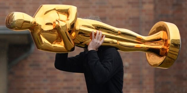 A worker carries an Oscar statue to a press event held by Filmstudios Babelsberg in Potsdam, eastern Germany following the sucess of the 'Grand Budapest Hotel' at the Oscars on February 23, 2015. The film, which was awarded 4 Oscars, Best original soundtrack, Best costume design, Best make-up / hairstyling and Best production design, was co-produced by Filmstudios Babelsberg. AFP PHOTO / DPA / RALF HIRSCHBERGER   +++ GERMANY OUT +++        (Photo credit should read RALF HIRSCHBERGER/AFP/Getty Images)
