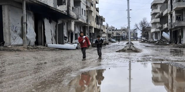 ALEPPO, SYRIA - FEBRUARY 18: Kids walking among the destroyed buildings of the Syrian town of Kobani (Ayn al-Arab), Aleppo on February 18, 2015  after it has been freed from Islamic State of Iraq and the Levant (ISIL) forces. While civilians in the eastern parts of the city are refusing entrance to the area on suspicion of a trap, houses in other areas are being presented ready for use by their owners. (Photo by Esber Ayaydin/Anadolu Agency/Getty Images)
