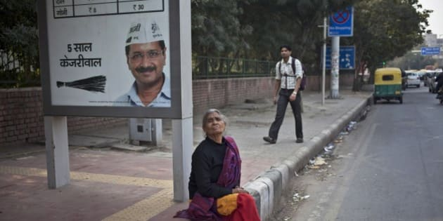 "An Indian woman waits for bus as she sits near an election advertisement with a photograph of Aam Aadmi Party leader Arvind Kejriwal at a bus stop in New Delhi, India, Sunday, Feb. 8, 2015. A slew of exit polls Saturday predicted an outright victory for Aam Aadmi Party, an upstart anti-corruption party in elections to install a state government in India's capital, a potentially huge blow for Prime Minister Narendra Modi's Hindu nationalist party. Hindi reads, ""five years Kejriwal"".(AP Photo/Tsering Topgyal)"
