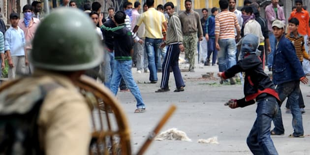 (FILES) In this photograph taken on June 12, 2010, Kashmiri protesters throw stones at Indian paramilitary soldiers during a protest in Srinagar. Indian Kashmir declared an amnesty on August 29, 2010 for more than 1,000 youths alleged to have attacked security forces during last year's pro-independence demonstrations in which more than 100 civilians died. Kashmir was rocked for months last summer by clashes between stone-throwing protesters and police and paramilitary troops, who used live fire to try to control massive rallies against New Delhi's rule over the region. AFP PHOTO/Rouf BHAT/ FILES (Photo credit should read ROUF BHAT/AFP/Getty Images)