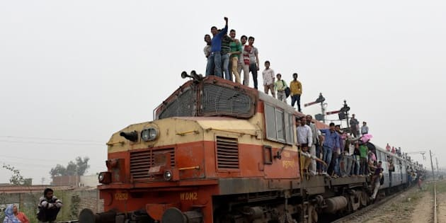 Indian passengers stand and hang onto a train as it departs from a station on the outskirts of New Delhi on February 25, 2015.  Indian Railways Minister Suresh Prabhu is scheduled to present the railway budget to parliament on February 26.    AFP PHOTO/MONEY SHARMA        (Photo credit should read MONEY SHARMA/AFP/Getty Images)