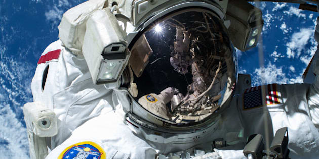"""ISS042E283176 (02/21/2015) -- NASA astronaut Barry """"Butch"""" Wilmore, Commander of Expedition 42 on Feb, 21, 2015 is caught by the camera as the Earth's surface passes by in the background. Wilmore and fellow astronaut Terry Virts (seen in the visor's reflection) completed a 6-hour, 41-minute spacewalk routing more than 300 feet of cable as part of a reconfiguration of the International Space Station to enable U.S. commercial crew vehicles under development to dock to the space station in the coming years."""