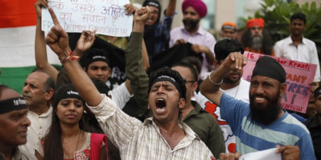 Indians shout slogans seeking death sentence for a juvenile convict who was earlier given a three-year in a reform home, after a judge pronounced death sentence for four others convicted in the rape and murder of a student on a moving New Delhi bus last year, in New Delhi, India, Friday, Sept. 13, 2013. The case has been closely followed across India, seen as a reflection on rampant mistreatment of women and the government's inability to deal with crime. (AP Photo/Altaf Qadri)