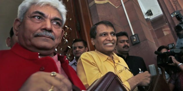 Indian Railway Minister Suresh Prabhu, centre, and junior Railway Minister Manoj Sinha, left, lifts the briefcases containing Railway budget for the year 2015-16 as they arrive at the parliament house to present it in New Delhi, India, Thursday, Feb. 26, 2015. Indian Railways is one of the world's largest and serves more than 23 million passengers a day. (AP Photo/Manish Swarup)