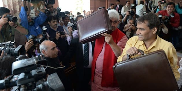 Indian Railways Minister Suresh Prabhu (R) and Minister of State for Railways Manoj Sinha (2R) pose for media as they arrive at Parliament House in New Delhi on February 26, 2015. India's rail minister has promised to revive railways through reforms, to take forward Prime Minister Narendra Modi's economic agenda, as he prepares to present his government's first rail budget. Suresh Prabhu said railways holds a pivotal place in his government's economic agenda as he hinted at major rail reforms in the budget. AFP PHOTO/ PRAKASH SINGH        (Photo credit should read PRAKASH SINGH/AFP/Getty Images)