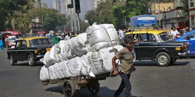 An Indian worker pulls a cart loaded with goods at a traffic intersection in Mumbai, India, Monday, Feb. 23, 2015. The government of Asia's third-largest economy is this week expected to present in Parliament the budget for the fiscal year ending March 2016. (AP Photo/Rafiq Maqbool)