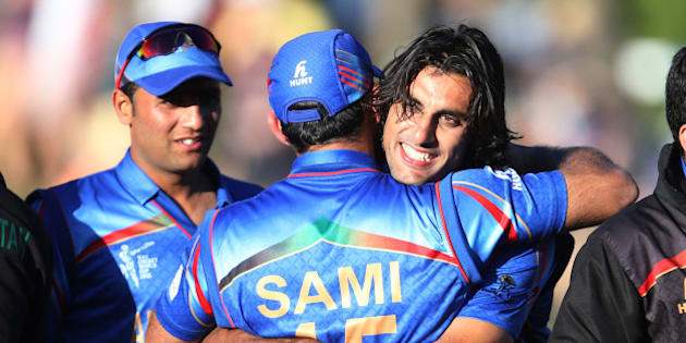 Afghanistan's Shapoor Zadran, right, embraces teammate  Samiullah Shenwari as he celebrates his team's Cricket World Cup Pool A win over Scotland in Dunedin, New Zealand, Thursday, Feb. 26, 2015. (AP Photo/Dianne Manson)