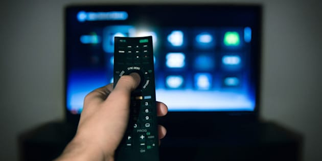 Hand of man pointing remote control at working television screen.