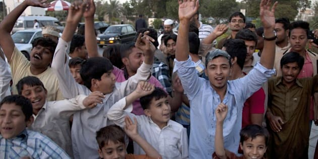 Pakistani cricket fans chant slogans to protest against the country's chief cricket selector Moin Khan at Karachi airport, Thursday, Feb. 26, 2015.  Khan returned home on the orders of Pakistan Cricket Board chairman Shaharyar Khan for dining out in a casino during World Cup in Christchurch, New Zealand last week. (AP Photo/Shakil Adil)
