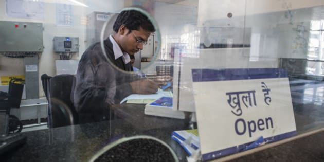An employee fills in paperwork behind a ticket counter at Sikanderpur Station, operated by Rapid MetroRail Gurgaon Ltd., in Gurgaon, Haryana, India, on Wednesday, Nov. 27, 2013. Data due on Nov. 29 may show Asias third-biggest economy expanded 4.6 percent from a year earlier in the quarter ended September, according to a Bloomberg survey, capping the longest quarterly stretch of sub-5 percent growth since 2005. Photographer: Prashanth Vishwanathan/Bloomberg via Getty Images