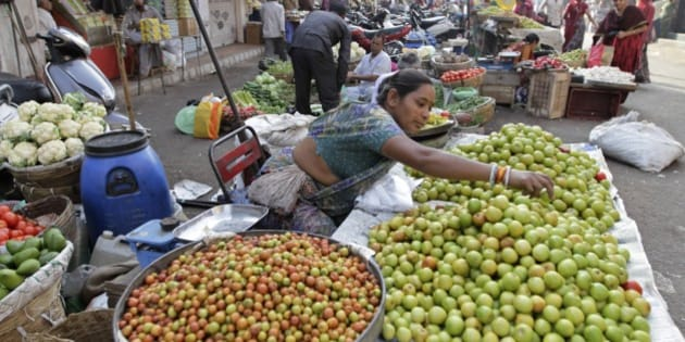 An Indian woman sells berries at a wayside vegetable market in Ahmadabad, India, Monday, Feb. 23, 2015. The government of Asia's third-largest economy is this week expected to present in Parliament the budget for the fiscal year ending March 2016. (AP Photo/Ajit Solanki)
