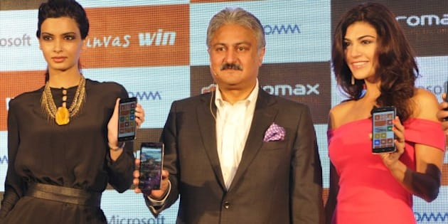 NEW DELHI, INDIA - JUNE 16: Bollywood actor Diana Panty (L), Sanjay Kapoor, Chairman Micromax (C) and Archana Vijaya during the launch of Micromax Canvas Win Series' two window bases phones Canvas Win W121 and Canvas win W092, on June 16, 2014 in New Delhi, India. Both are budget phones, with the former priced at Rs 6,500, while the latter will come for Rs 9,500. The Canvas Win W092 is believed to be the cheapset Windows Phone smartphone in India. Micromax has become the first Indian smart phone player to launch a window-based Phone. (Photo by Sushil Kumar/Hindustan Times via Getty Images)